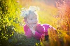 Gullig liten flicka som lägger i ett fält Fotografering för Bildbyråer