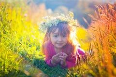 Gullig liten flicka som lägger i ett fält Arkivbilder