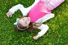 Gullig liten flicka som lägger i gräset Royaltyfri Fotografi
