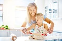 Gullig liten flicka som lär att rulla ut deg Arkivfoton