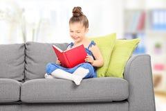 Gullig liten flicka som läser en bok i vardagsrummet Arkivfoto