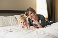 Gullig liten flicka som läser en bok med hennes moder i sovrummet royaltyfri bild