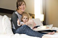 Gullig liten flicka som läser en bok med hennes moder i sovrummet arkivfoton