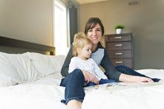 Gullig liten flicka som läser en bok med hennes moder i sovrummet royaltyfri foto