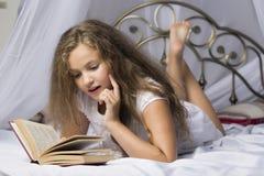 Gullig liten flicka som läser en bok och ler, medan ligga på en säng i rummet royaltyfri foto