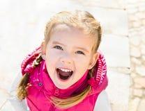 Gullig liten flicka som ler i en park arkivfoton