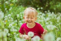 Gullig liten flicka som ler med maskrosor Royaltyfri Fotografi