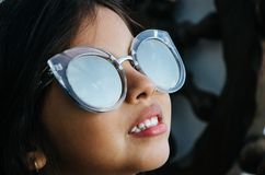 Gullig liten flicka som ler med solglasögon Arkivbild