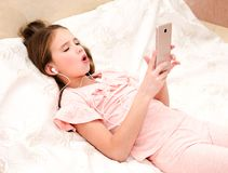 Gullig liten flicka som ligger på sängen som lyssnar till musik och att sjunga arkivbilder