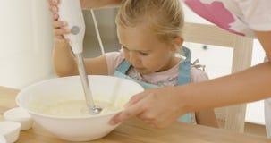 Gullig liten flicka som lär att baka från moder Royaltyfri Bild