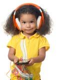 Gullig liten flicka som lyssnar till musik på en mobiltelefon Fotografering för Bildbyråer