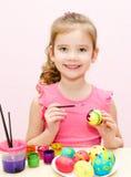 Gullig liten flicka som målar easter ägg royaltyfri foto