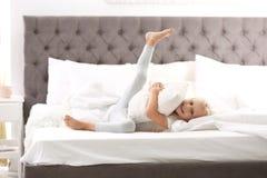 Gullig liten flicka som omfamnar kudden på säng arkivbild
