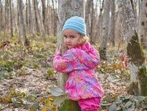 Gullig liten flicka som på våren kramar en skog för trädstam fotografering för bildbyråer