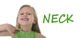 Gullig liten flicka som pekar hennes hals i kroppsdelar som lär engelskaord på skolan Fotografering för Bildbyråer