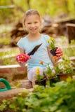 Gullig liten flicka som planterar blommor arkivbild