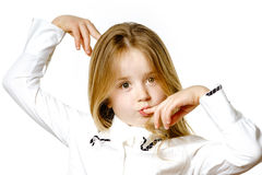 Gullig liten flicka som poserar för annonsering som gör signes vid händer Royaltyfri Foto