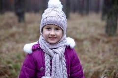 Gullig liten flicka som poserar i höstskog på det torra gräset Arkivbilder