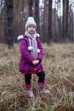 Gullig liten flicka som poserar i höstskog på det torra gräset Royaltyfria Bilder