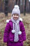 Gullig liten flicka som poserar i höstskog på det torra gräset Fotografering för Bildbyråer