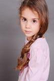 Gullig liten flicka som poserar på grå färger i rum Royaltyfria Foton