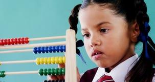 Gullig liten flicka som räknar på kulrammet arkivfilmer