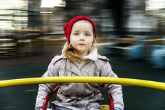 Gullig liten flicka som rundar på karusell Arkivfoto