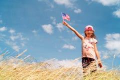 Gullig liten flicka som rymmer en amerikanska flaggan Royaltyfri Foto