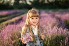 Gullig liten flicka som rymmer en bukett av lavendel Royaltyfri Fotografi