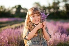 Gullig liten flicka som rymmer en bukett av lavendel Fotografering för Bildbyråer