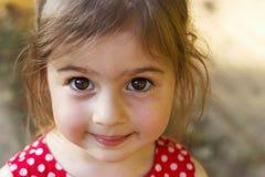 Gullig liten flicka som ser den förvånade kameran Lycklig unge ut fotografering för bildbyråer