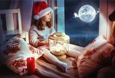 Gullig liten flicka som ser månen vinterhimlen arkivfoto