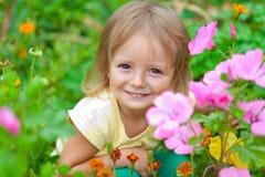 Gullig liten flicka som sitter bland blommorna arkivfoton