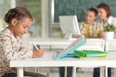 Gullig liten flicka som sitter i klassrum med läraren och skolpojken royaltyfri foto