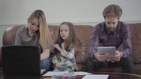 Gullig liten flicka som sitter mellan modern och faderteckningen med kulöra markörer Ung kvinna som skrivar p? henne b?rbar dator stock video