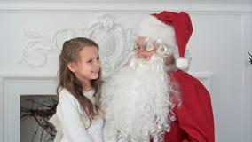 Gullig liten flicka som sjunger ett julsångsammanträde på den Santa Claus varven Royaltyfria Bilder