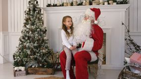 Gullig liten flicka som sjunger ett julsångsammanträde på den Santa Claus varven Arkivfoton