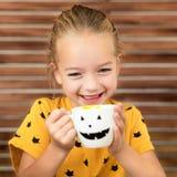 Gullig liten flicka som skrattar och dricker pumpasoppa ut ur en kopp med den anthropomorphic smileyframsidan för allhelgonaafton arkivbilder