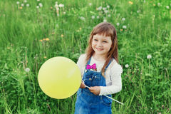 Gullig liten flicka som skrattar och rymmer leksakballongen i hand på den gröna ängen utomhus- lyckligt barndombegrepp fotografering för bildbyråer