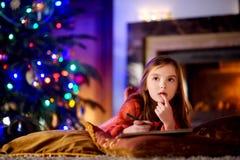 Gullig liten flicka som skrivar ett brev till jultomten vid en spis på jul Royaltyfri Foto