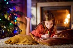 Gullig liten flicka som skrivar ett brev till jultomten vid en spis på jul arkivfoto