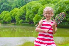Gullig liten flicka som spelar badminton på picknick Arkivfoton