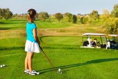 Gullig liten flicka som spelar golf på ett utomhus- fält Royaltyfri Foto