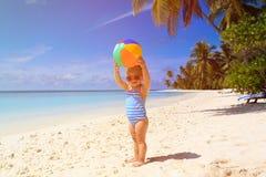 Gullig liten flicka som spelar med bollen på stranden arkivbilder