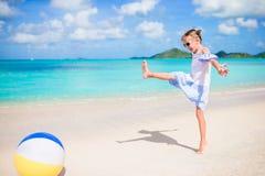 Gullig liten flicka som spelar med bollen på stranden, ungesommarsport utomhus arkivfoto