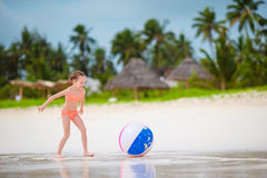 Gullig liten flicka som spelar med bollen på stranden, ungesommarsport utomhus Fotografering för Bildbyråer
