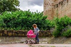 Gullig liten flicka som spelar med dockan och som är mer babycarrier i parkera Royaltyfria Bilder
