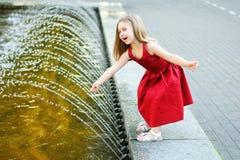 Gullig liten flicka som spelar med en stadsspringbrunn på varm och solig sommardag Royaltyfri Fotografi