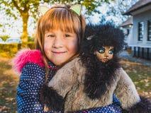 Gullig liten flicka som spelar med hennes utomhus- favorit- docka-kissekatt Aut fotografering för bildbyråer