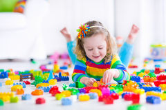 Gullig liten flicka som spelar med leksakkvarter Royaltyfri Foto